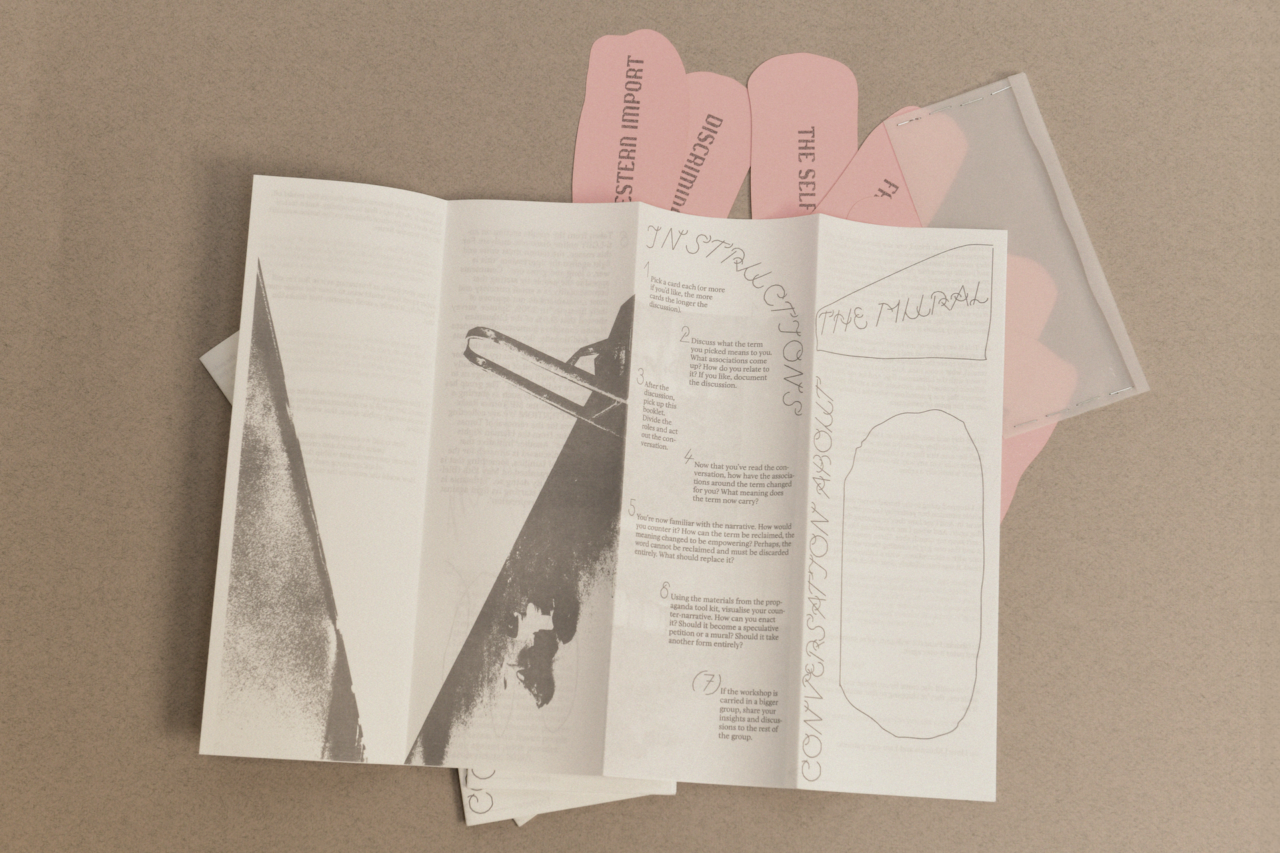 The image shows a booklet from the workshop. On the booklet we see an image of a wall, with the mural cut-out. On the other side, you can find the instructions on how the workshop is carried out. Below the open booklet, there are pink cards spread out. Next to them is a transparent envelope.